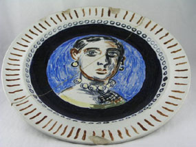 Painted plate with a portrait of a woman in the center of the plate.