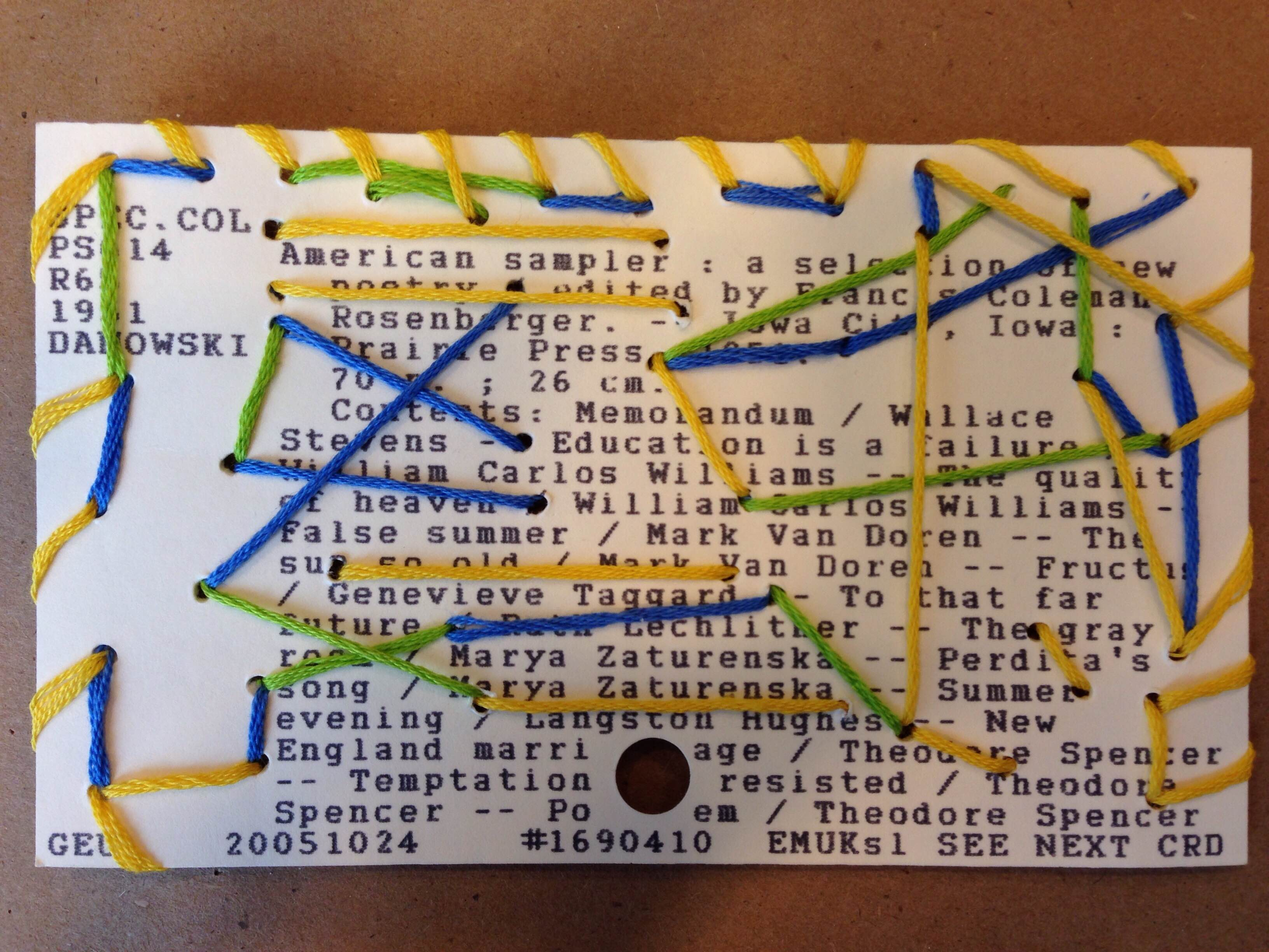 Card catalog card sewn in a random pattern with green, blue, and yellow embroidery thread.