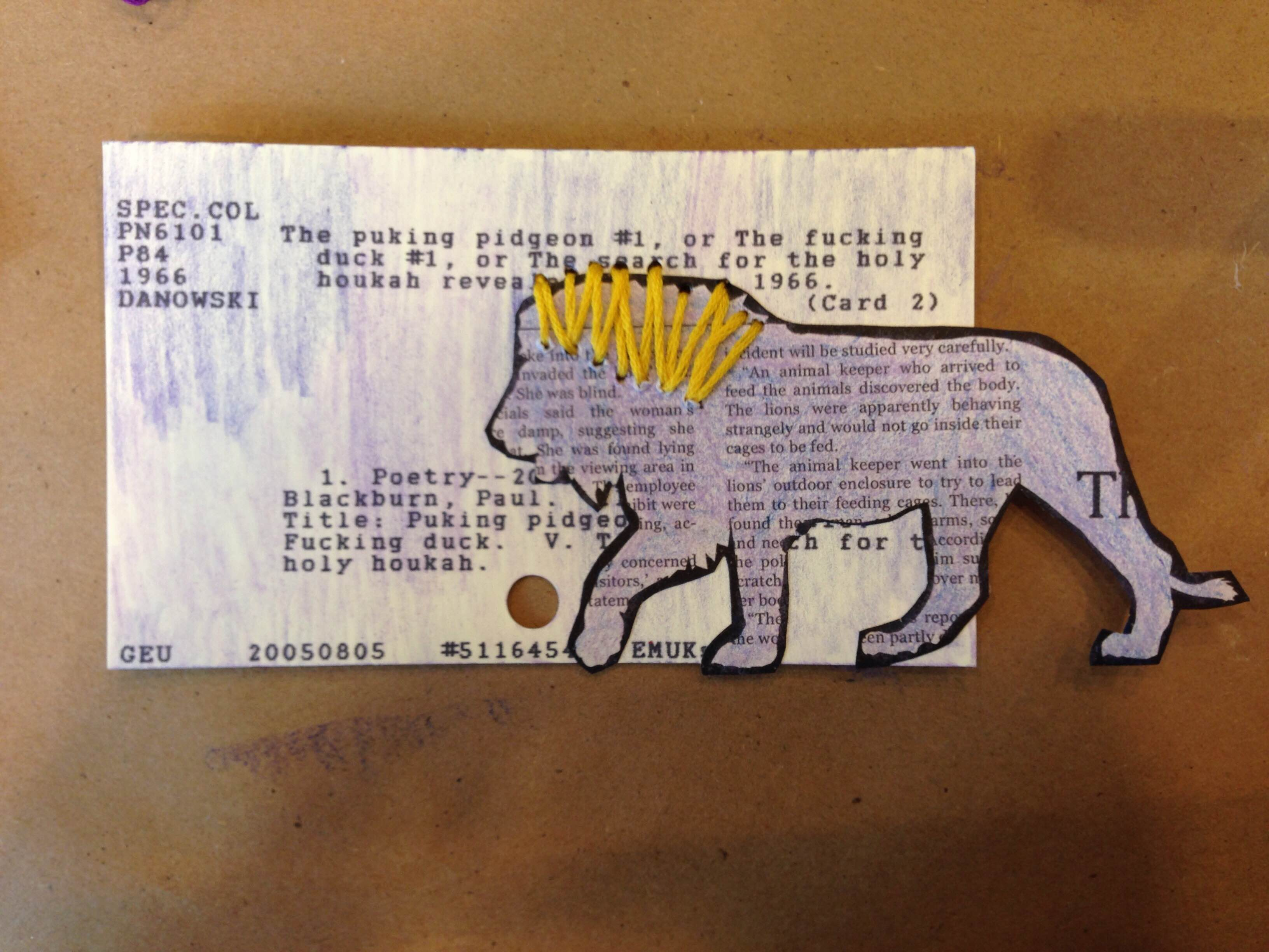 Card catalog decorated with shades of purple colored pencil, a cutout lion with a sewn yellow embroidery thread mane.
