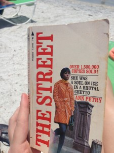 "A hand holds a paperback copy of Ann Petry's The Street in the forefront of the image, with sand and beach chairs in the background. The tagline on the cover reads, ""She was a soul on ice in a brutal ghetto"" and ""over 1,500,000 copies sold!"""
