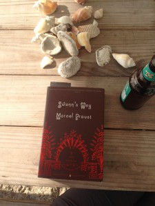 A paperback copy of Swann's Way (brown cover, with red ornate design details), on a wooden table with several sea shells and a bottle of beer.