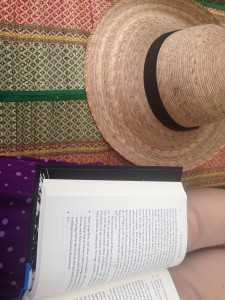 An open book on the lap of someone sitting on a colorful woven mat, beside a round straw hat.