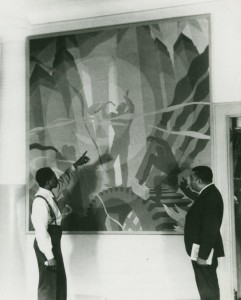 "Schomburg Center for Research in Black Culture, Photographs and Prints Division, The New York Public Library. ""Artist Aaron Douglas (left) and Schomburg Collection curator Arthur A. Schomburg in front of Douglas's painting ""Aspects of Negro Life: Song of the Towers""."" The New York Public Library Digital Collections. 1934."
