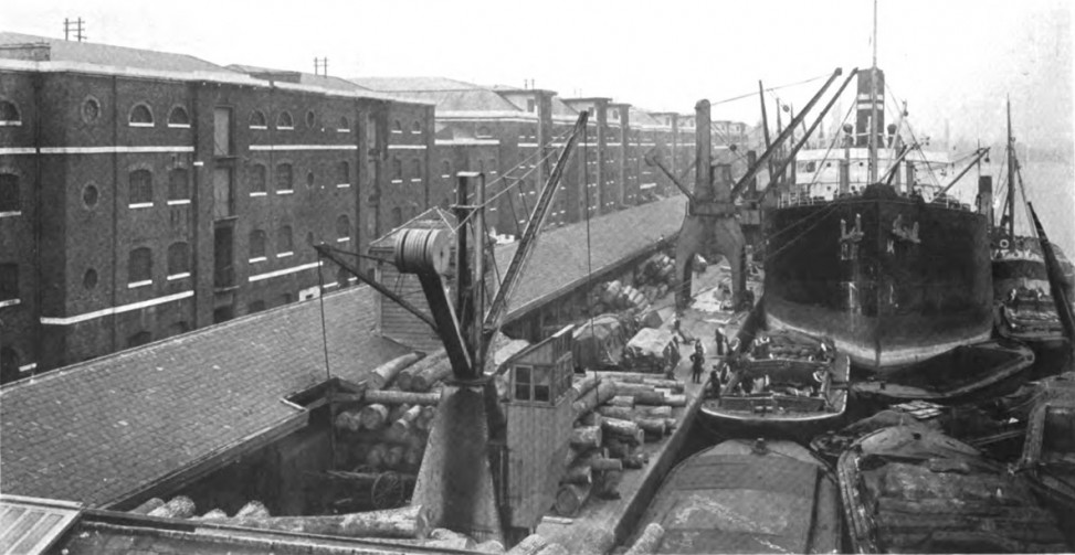 Black and white photograph of a dock with a tall ship with cargo being loaded or unloaded beside it, on the dock. Brick buildings flank the dock.