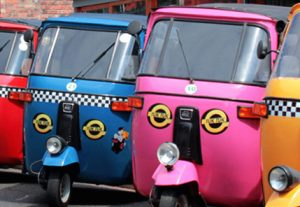 A row of colourful tuk-tuk, three-wheel vehicles.