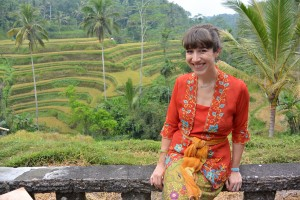 Jennifer in traditional Balinese kabaya top, sarong, and sash overlooking rice fields near the program's outdoor classroom in Ubud, Bali.