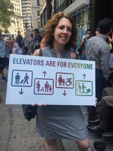 """Photo of Jessica Murray holding a sign that says """"Elevators are for Everyone"""" with icons of various people who use elevators inside boxes with arrows representing elevators moving up and down. The icons represent a person with crutches, a person rolling a suitcase, a pregnant woman, a person with a heart condition, a young girl, a woman and young boy, a wheelchair user, a person with a cane, and a delivery person rolling a cart with packages."""