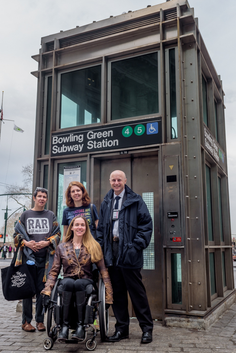Photo of four people in front of the Bowling Green subway station elevator, one of few wheelchair accessible stations in downtown Manhattan. Front, April Coughlin, who uses a manual wheelchair. Back, Jennifer Marie Bartlett, Jessica Murray, and Andy Byford, NYCT President.