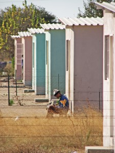 Figure 5. Young man sits outside row of concrete houses in center of Tsumkwe, Namibia.